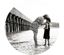 mother kisses little girl on beach