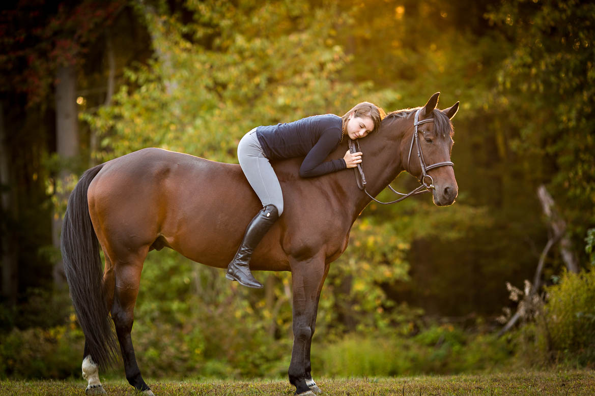 Girl snuggles horse in the fall sunlight