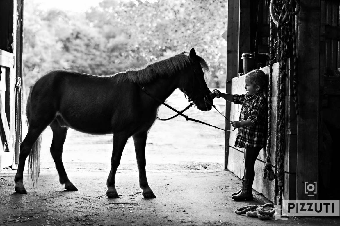 Little girl brushes her pony
